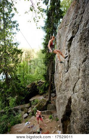 A female climber, repelling down a steep rock face (crag)