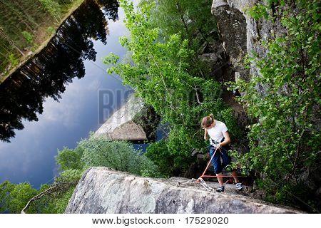 Ein weiblicher Kletterer, Abwehr, eine steile Felswand (Fels)