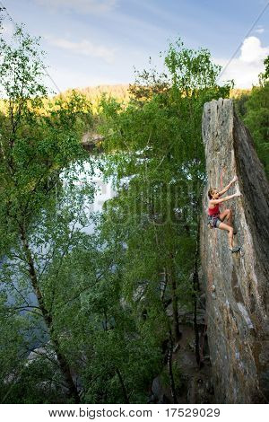 An eager female climber on a steep rock face looks for the next hold. Breathtaking scenery including a lake and forest are in the background.