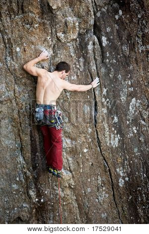 A male climber against a large rock face climbing lead.