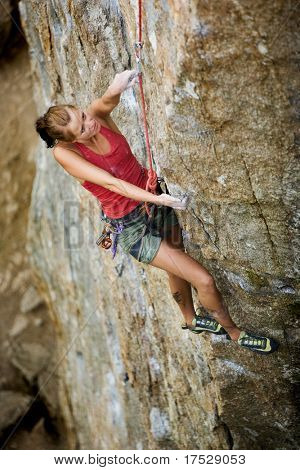 Female rock climber reaching for the next hold.
