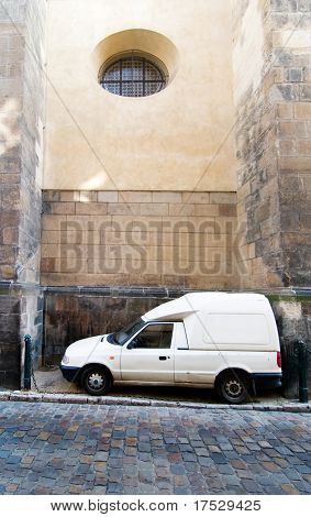 A humorous image of a cargo truck parked between two large buttresses at the St. Giles Church, Prague, Czech Republic.
