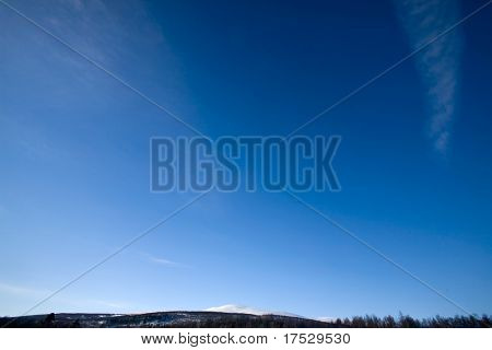 A deep blue sky background with faint clouds and a sliver of mountains
