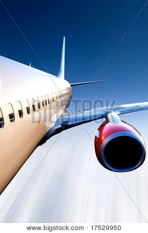 An airplane in flight over a blue sky