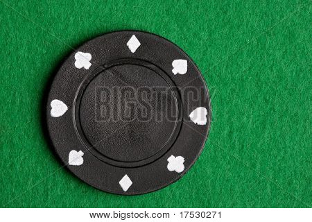 A black $100 poker chip on green felt