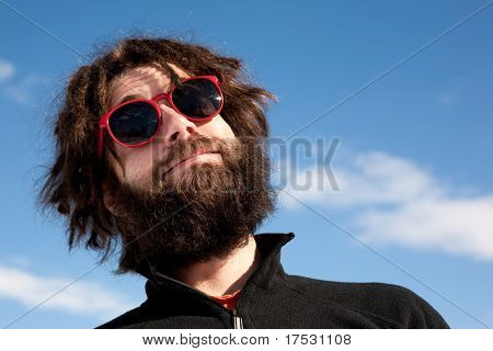 A funny portrait of a male with a full beard and sunglasses