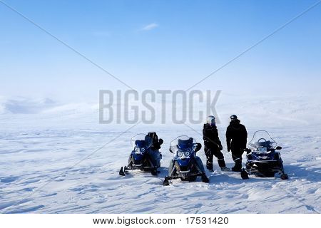 A barren winter landscape with a group of people on a snowmobile expedition