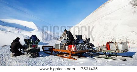 People preparing snowmobiles for an expedition through through winter conditions