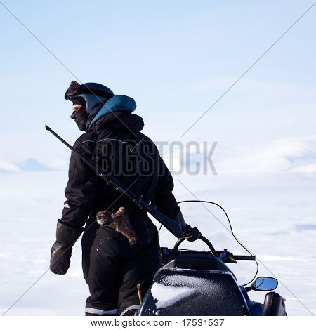 An arctic guide equiped with a rifle, looks out on the horizon