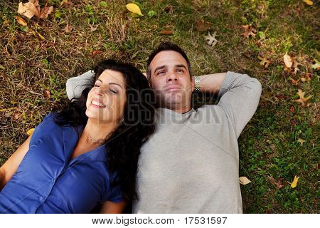 A couple laying on grass in a park daydreaming.  Focus on the woman's eyes