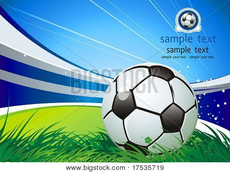 Soccer ball on green grass over a natural clear blue sky background