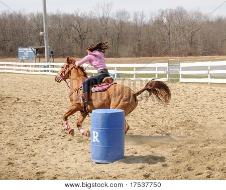 Young woman barrel racing