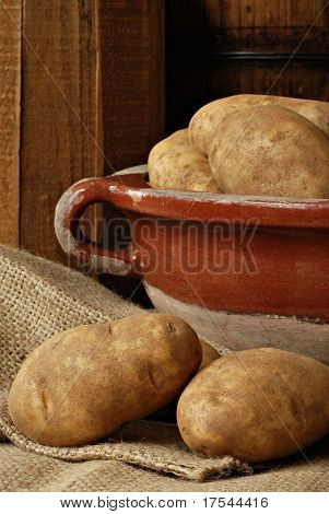 Rustic still life of potatoes on burlap with stoneware bowl against wood background.  Closeup with shallow dof.