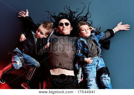 Heavy metal musician  with children lying on a floor. Shot in a studio.