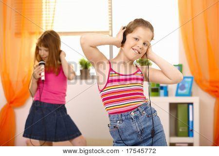 Girls enjoying music, listening via headphones, singing with microphone, dancing.?