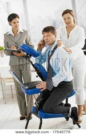 Businessman talking on mobile while getting neck massage in office.?