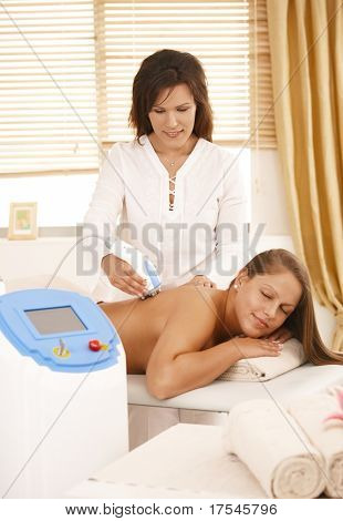 Masseur doing radio frequency fat reduction treatment in day spa.?