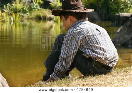 Child Sitting By Outback Billabong