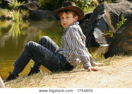 Rural Boy Sitting By Banks Of A River