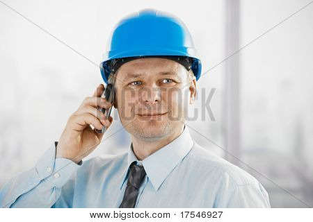 Portrait of architect talking on mobile, looking at camera, smiling.?