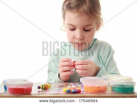 Niña sentada en la mesa y cuidadosamente esculpido hace figuras de plastilina
