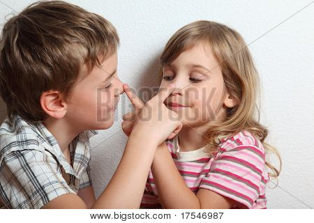 Portrait of playful little girl and boy, they put fingers on nose of each other