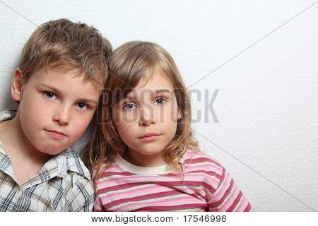 Portrait of thoughtful little girl and boy, they put heads on each other