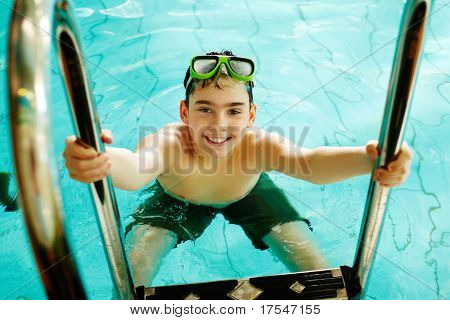 Photo of happy teenage lad in pool smiling at camera