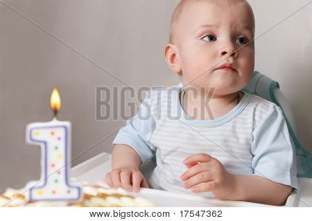 "Little baby celebrating its first birthday, in front of him cake with candle in the form of ""1"""