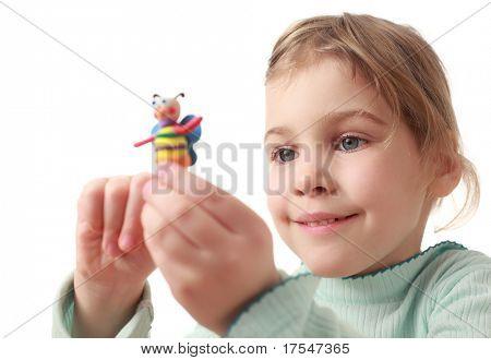 Niña feliz sostiene modelar plastilina hecha a mano - abeja colorido