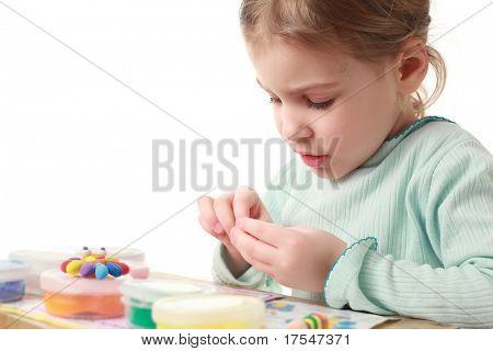 Vista lateral de la niña sentada en la mesa y cuidadosamente esculpe figuras de plastilina