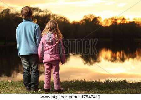 Little girl in pink clothes and boy in blue jacket holding hands and standing back on bank of river and admire on sunset