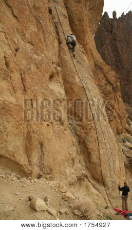Woman Belaying A Climber On Rock Face