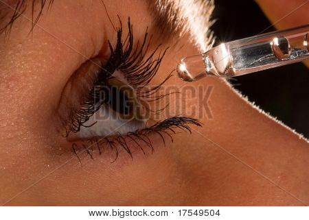 woman`s eye and eyedropper with waterdrop on tip