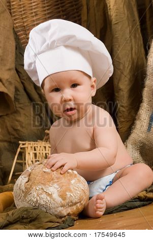 child with bread on bakery-like background wearing cook-hat