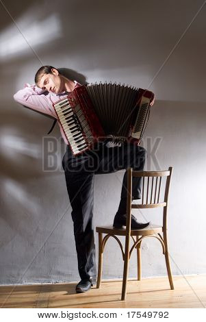 accordion player with chair on the lightened wall background
