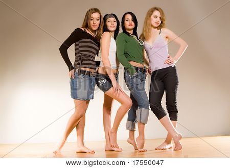 four girls standing on the wood floor with bare feets. Photo is a part of small sequented serie