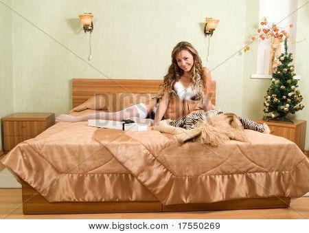 junge blonde Frau im weißen Pelzmantel und schwarzer Bikini machen ein Handy Call und eines Mannes mit weißen gi