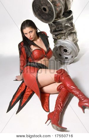Pretty young woman in red leather coat lying close to metal barrels