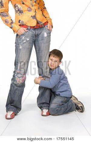 Boy holding his mom leg isolated on white background