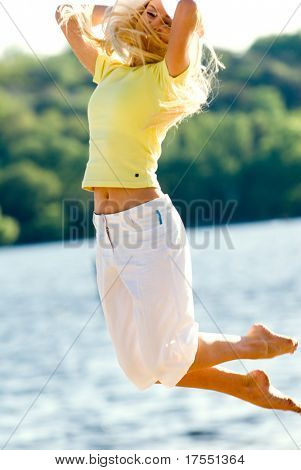 Nice young girl jumping on the beach