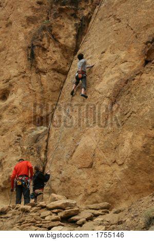Woman Belaying A Climber On Rock Face