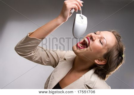 Pretty young caucasian girl pretending to eating computer mouse