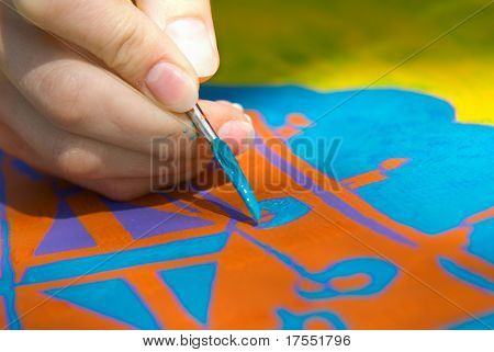 Artist fingers with brush, doing artwork