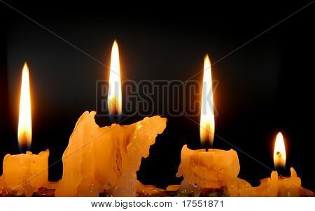Row of burning candles in darkness