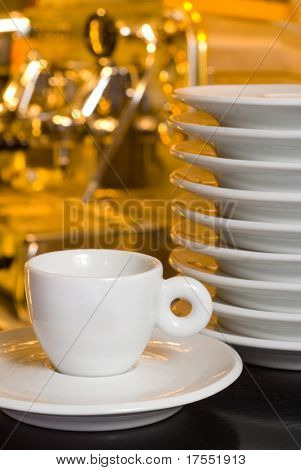 Coffee cup with plates on the blurred coffe-mashing background