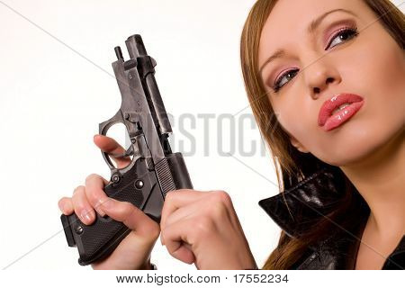 Sexy young woman with a gun isolated on white