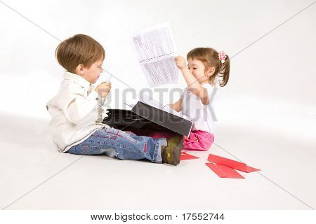 Pretty little kids playing with suitcase and papers