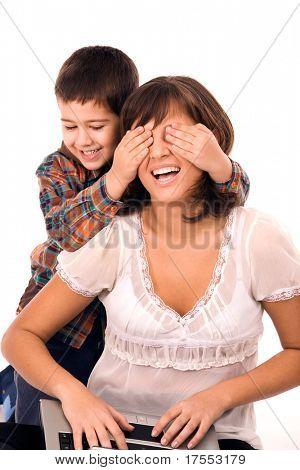 Madre e hijo jugando hide and seek y trabajando en equipo portátil