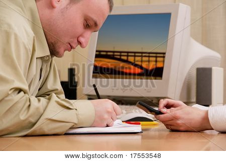 Businessman writing down notes at office